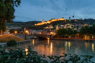 Bridge across the Kura River and illuminated fortress on hill, Tbilisi, Georgia, at sunset.の写真素材 [FYI02706619]
