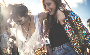 Two young women at a summer music festival wearing sequins with painted faces laughing and dancing.の写真素材 [FYI02706626]