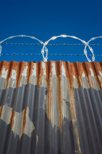 Low angle view of worn corrugated metal fence, razor wire above.の写真素材 [FYI02706630]