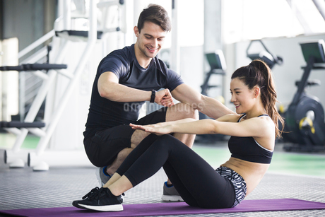 Young woman working with trainer at gymの写真素材 [FYI02706635]