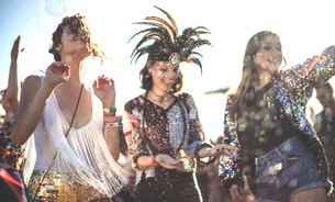 Three smiling young women at a summer music festival face painted, wearing feather headdress, dancinの写真素材 [FYI02706639]