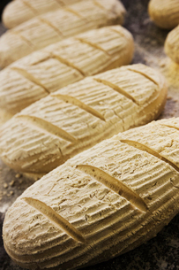 Close up high angle view of bread dough shaped into loaves, dusted with flour.の写真素材 [FYI02706641]