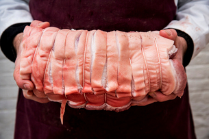 Close up of butcher wearing apron holding large rolled pork belly.の写真素材 [FYI02706642]