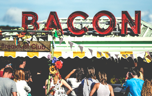 Revellers at a ood stall at a summer music festival red neon sign advertising bacon.の写真素材 [FYI02706643]