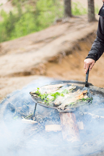 Cooking fish over a campfireの写真素材 [FYI02706648]