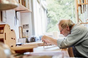 A violin maker at his drawing board drawing out the plans and outline for a new instrument.の写真素材 [FYI02706657]
