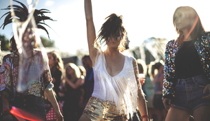 Young woman at a summer music festival wearing golden sequinned hot pants, dancing among the crowd.の写真素材 [FYI02706658]