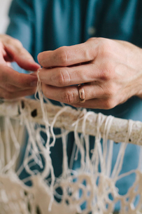 An artist working on an art piece hanging on a frame, knotting and weaving threads.の写真素材 [FYI02706671]
