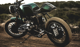 Green cafe racer motorcycle parked on the side of a dirt road.の写真素材 [FYI02706685]
