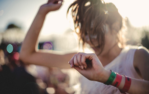 Young woman with long brown hair at a summer music festival dancing.の写真素材 [FYI02706691]