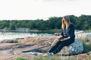 Mid adult woman reading outdoors in Karlskrona, Swedenの写真素材 [FYI02706711]