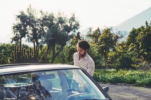 Mid adult man by Mercedes-Benz carの写真素材 [FYI02706714]