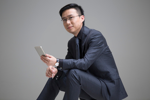 Mid adult businessman holding a smart phoneの写真素材 [FYI02706719]