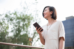 Beautiful young Chinese woman holding a smart phoneの写真素材 [FYI02706727]