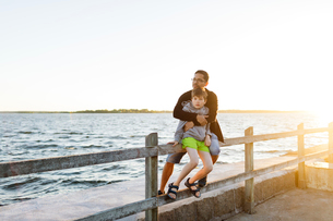 Father and son sitting on a pier at sunset in Blekinge, Swedenの写真素材 [FYI02706728]