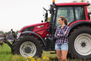 Agricultural worker standing in front of tractorの写真素材 [FYI02706734]