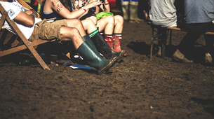People sitting on deckchairs in the mud, wearing Wellington boots,  at a summer music festival.の写真素材 [FYI02706736]