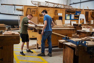 Two men standing at a workbench in a boat-builder's workshop, working on piece of wood.の写真素材 [FYI02706738]