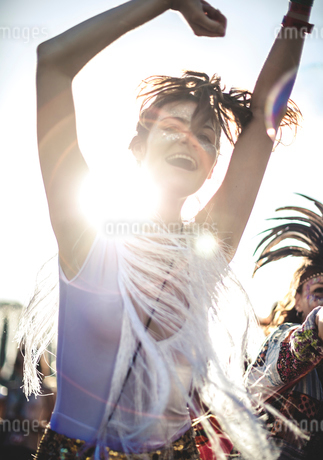 Young woman at a summer music festival arms raised, dancing among the crowd.の写真素材 [FYI02706740]