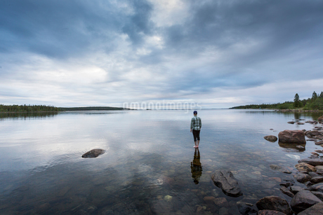 Man standing on rock by a lake in Vasterbotten, Swedenの写真素材 [FYI02706751]