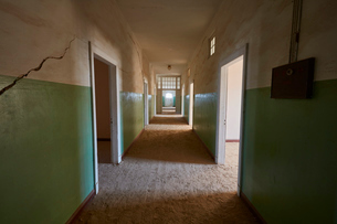 A view of a corridor in a derelict building full of sand. Vivid green coloured walls. Shadowsの写真素材 [FYI02706754]