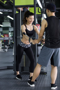 Young woman working with trainer at gymの写真素材 [FYI02706757]
