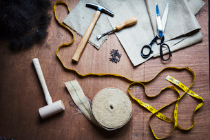 Upholstery workshop. Overhead view of hand tools, hammer, tape, tape measure and scissors.の写真素材 [FYI02706765]