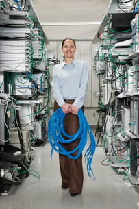 Female computer technician holding CAT 5 cables and standing in the aisle of a computer server farm.の写真素材 [FYI02706767]