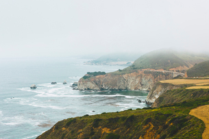 USA, California, Big Sur, Bixby Creek Bridge, Rocky coast with bridge in distanceの写真素材 [FYI02706781]