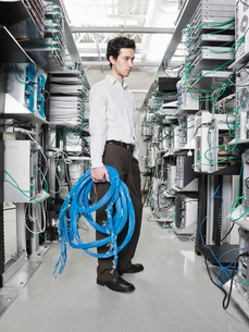 Male computer technician holding CAT 5 cables and standing in the aisle of a computer server farm.の写真素材 [FYI02706801]