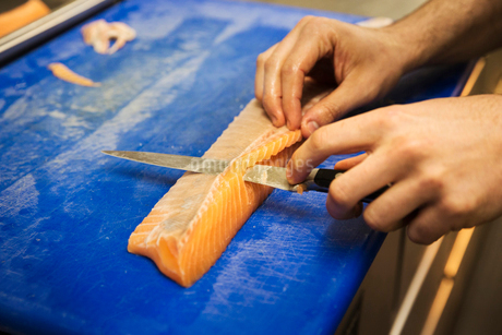 Close up high angle view of person, cutting a fillet of salmon on a blue chopping board.の写真素材 [FYI02706828]