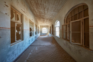 A view of a corridor in a derelict building full of sand.の写真素材 [FYI02706830]