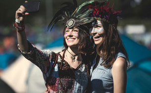 Two young women at a summer music festival faces painted, wearing feather headdress, taking selfie wの写真素材 [FYI02706849]
