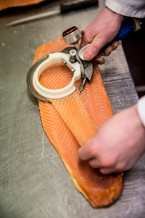 High angle close up of fishmonger using special slicer to thinly slice fillet of salmon.の写真素材 [FYI02706865]