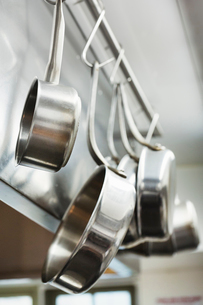 Close up of stainless steel pots and pans hanging on metal hooks on a shelf in a restaurant kitchen.の写真素材 [FYI02706882]