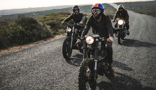 Three men wearing open face crash helmets and goggles riding cafe racer motorcycles along rural roadの写真素材 [FYI02706904]