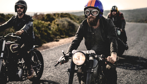 Three men wearing open face crash helmets and goggles riding cafe racer motorcycles along rural roadの写真素材 [FYI02706907]