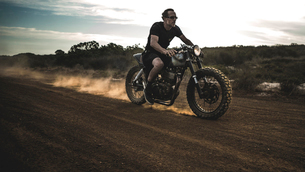Man wearing shorts and sunglasses riding cafe racer motorcycle on a dusty dirt road.の写真素材 [FYI02706908]