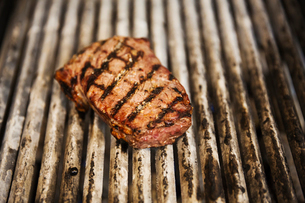 Close up high angle view of a steak on a griddle.の写真素材 [FYI02706912]