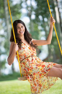 pretty, mid-adult woman on outdoor swingの写真素材 [FYI02706953]