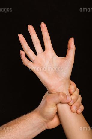 Male hand grabbing female wristの写真素材 [FYI02707382]
