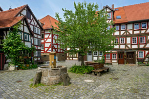 Half-timbered houses and fountain on a small squareの写真素材 [FYI02707400]
