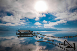 Sunlight through cloud; lake refection; cabin at the lake with pray flag line. Napa Hai Nature Reserの写真素材 [FYI02707577]