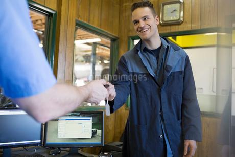 Mechanics exchanging keys auto shop officeの写真素材 [FYI02708091]