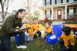 Coach and boys sports team gathering recycling neighborhoodの写真素材 [FYI02708116]