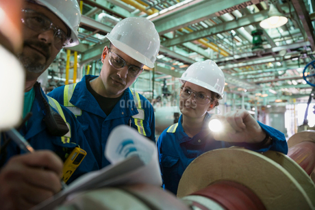 Workers with paperwork inspecting equipment at gas plantの写真素材 [FYI02708175]