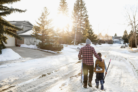 Father and son walking with ice hockey sticks and ice skates on snowy roadの写真素材 [FYI02708179]