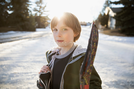 Portrait confident, serious boy holding ice hockey stick and ice skates on sunny, snowy roadの写真素材 [FYI02708338]