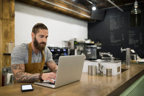 Hipster barista working at laptop in coffee shopの写真素材 [FYI02708471]
