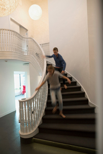 Brother chasing sister down foyer staircaseの写真素材 [FYI02708594]